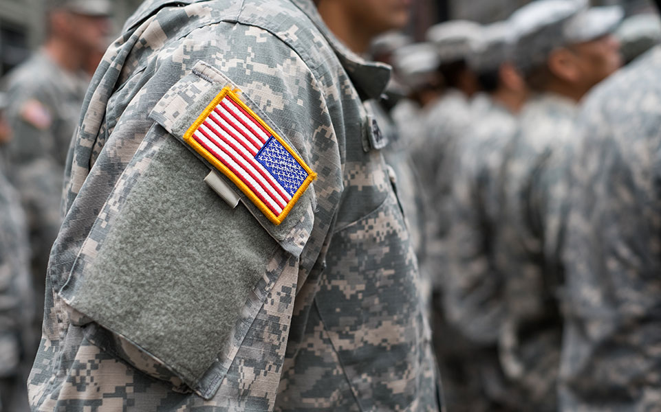 A soldier stands in uniform, bearing the American flag patch.