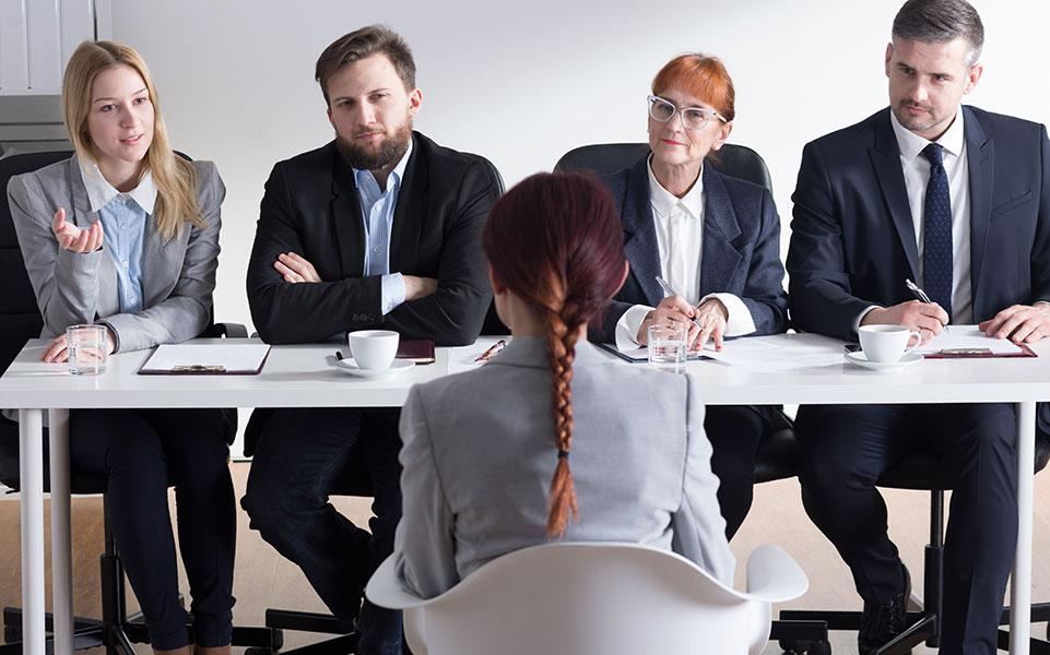 A woman sits through an uncomfortable job interview.