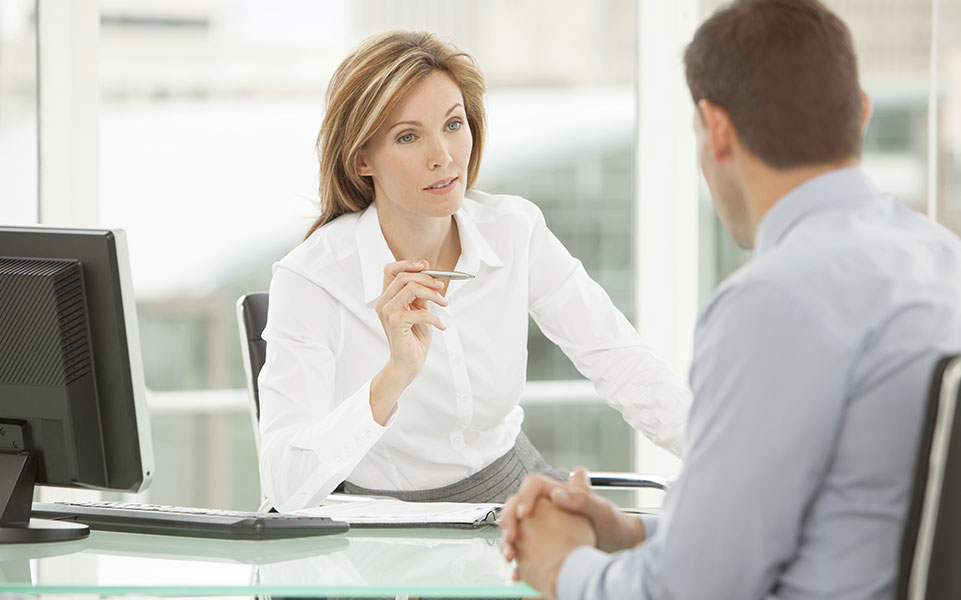A woman interviews a man as they review his resume.