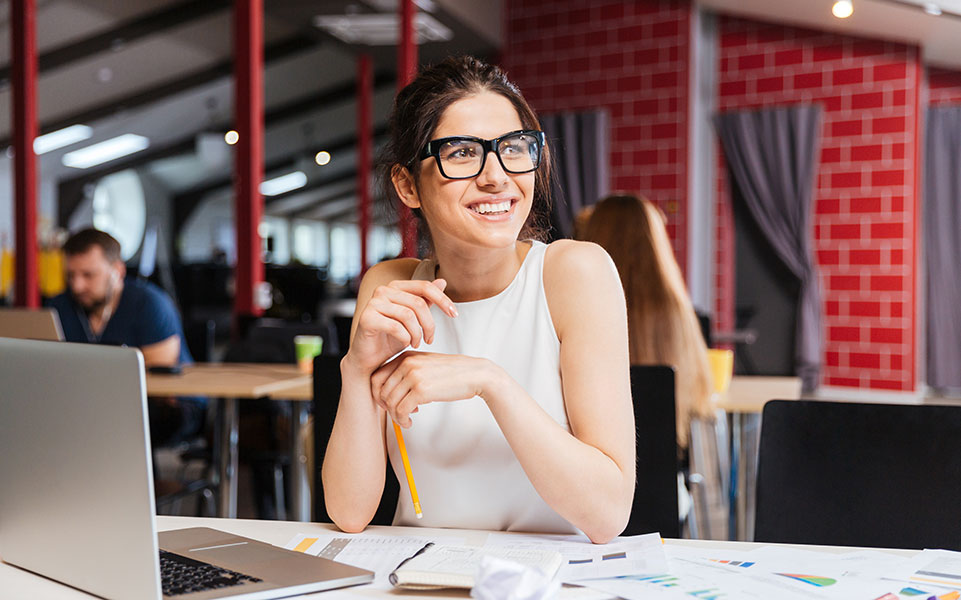 A female intern smiles at her desk.