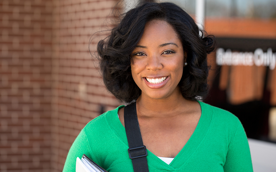A female, African American student smiles.