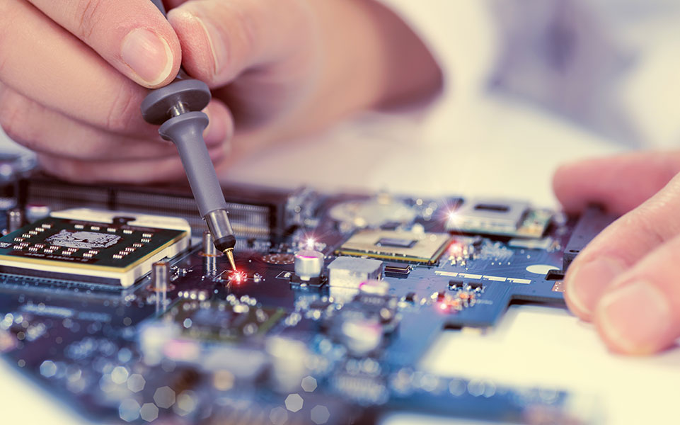 An electrical engineer works on a circuit board.