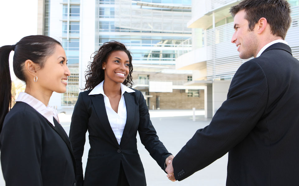 Two recruiters greet and job candidate.