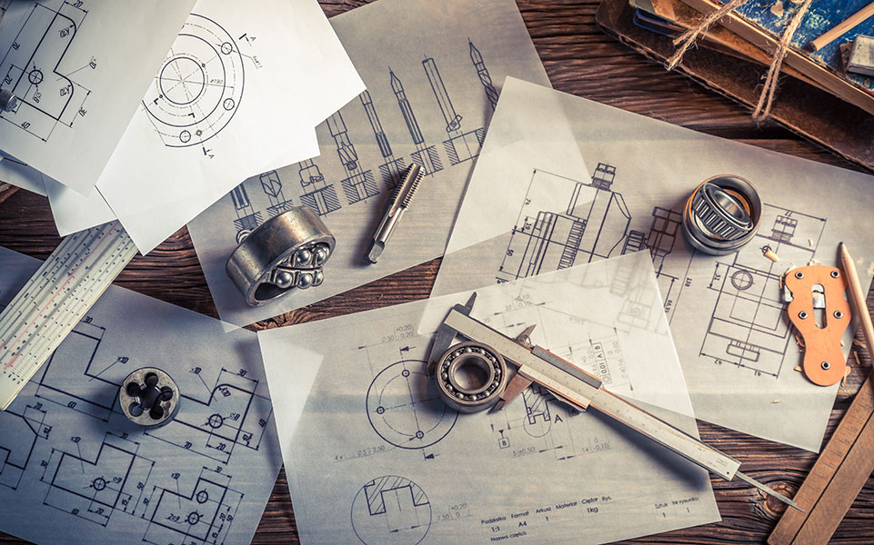 Engineering tools and blueprints are scattered on a table.