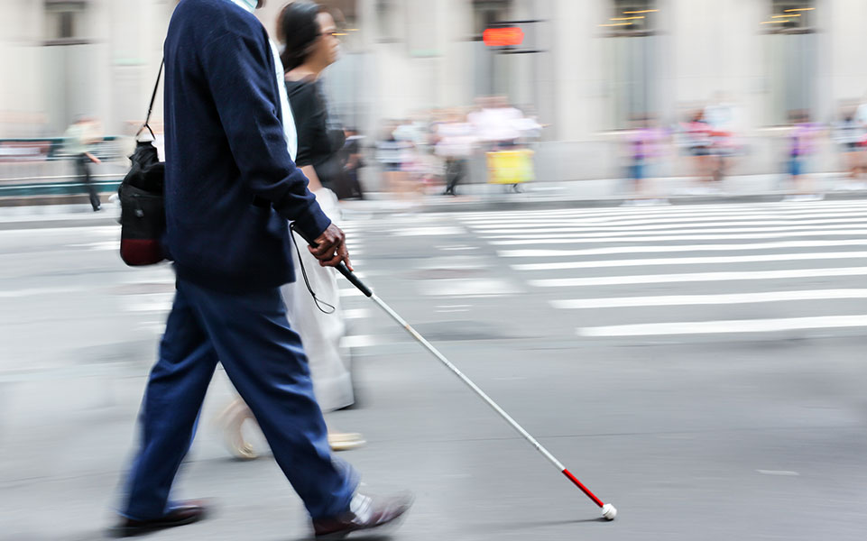 A blind man walks to work.