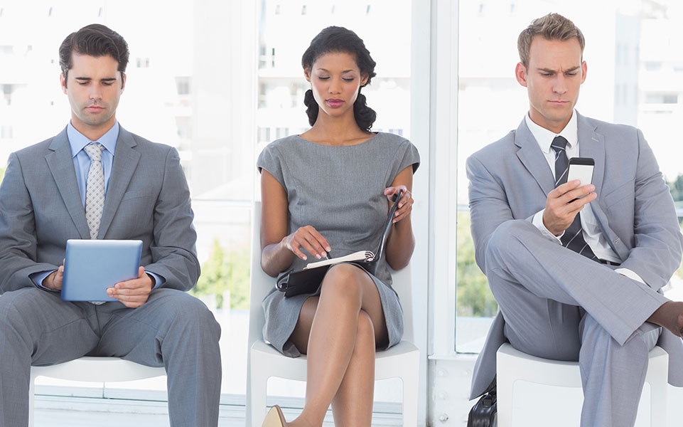 A woman sits between two men awaiting a job interview at an engineering firm.