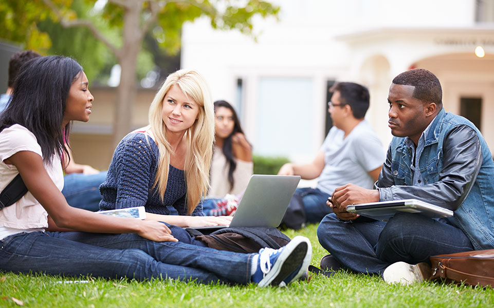 Graduate students sit on campus, discussing life after graduation.