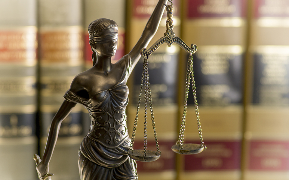 A scale sits in front of a set of legal books.