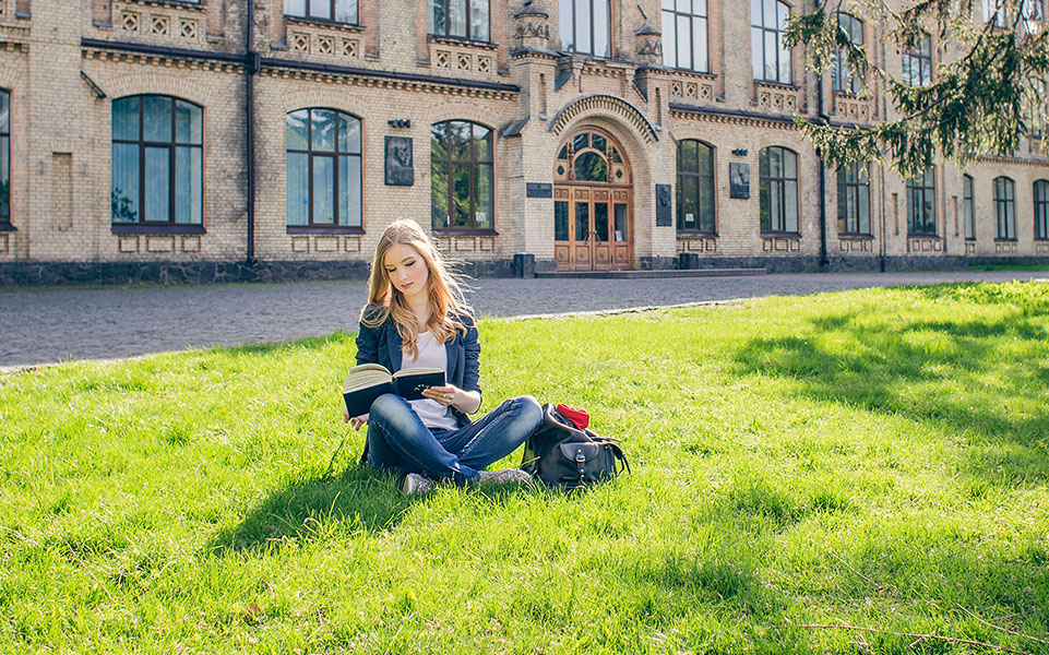 A college student reads a book on the campus lawn.