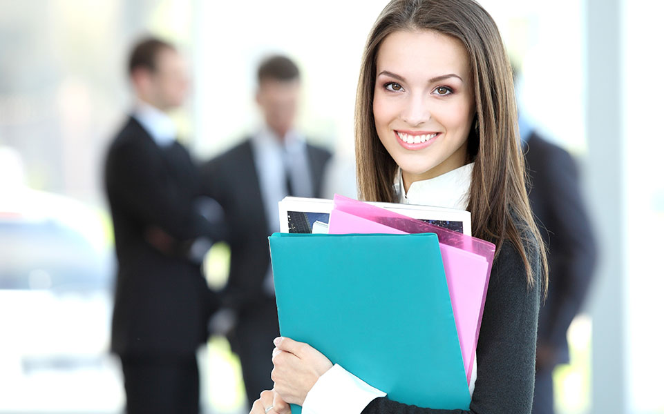 A woman carries some file folders containing her company's onboading plan.