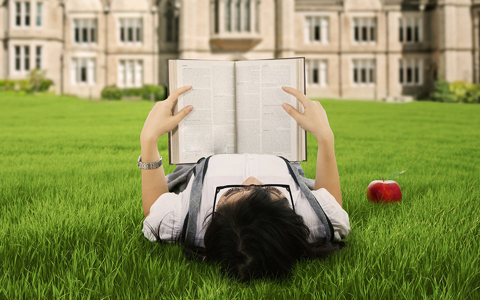 A philosophy student reads a book on the campus lawn.