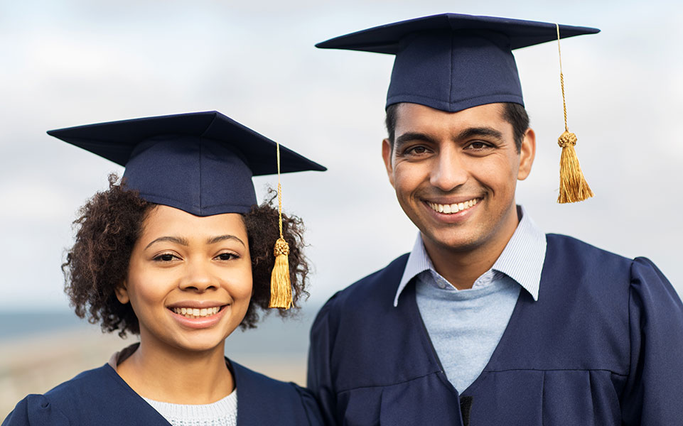 Two advanced degree college graduates smile on graduation day.