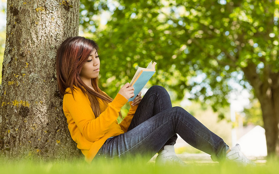 A college student reads a book about career planning.