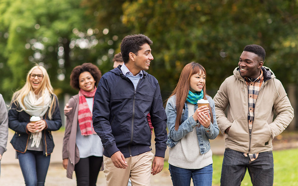 A group of international students walk on their college campus.