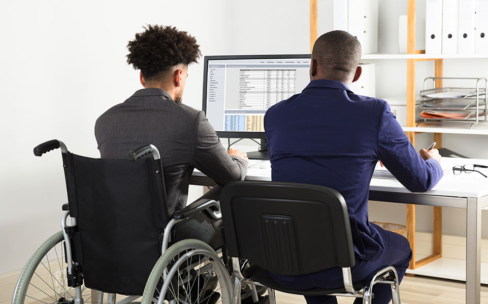 Two coworkers work together; one is in a wheelchair.