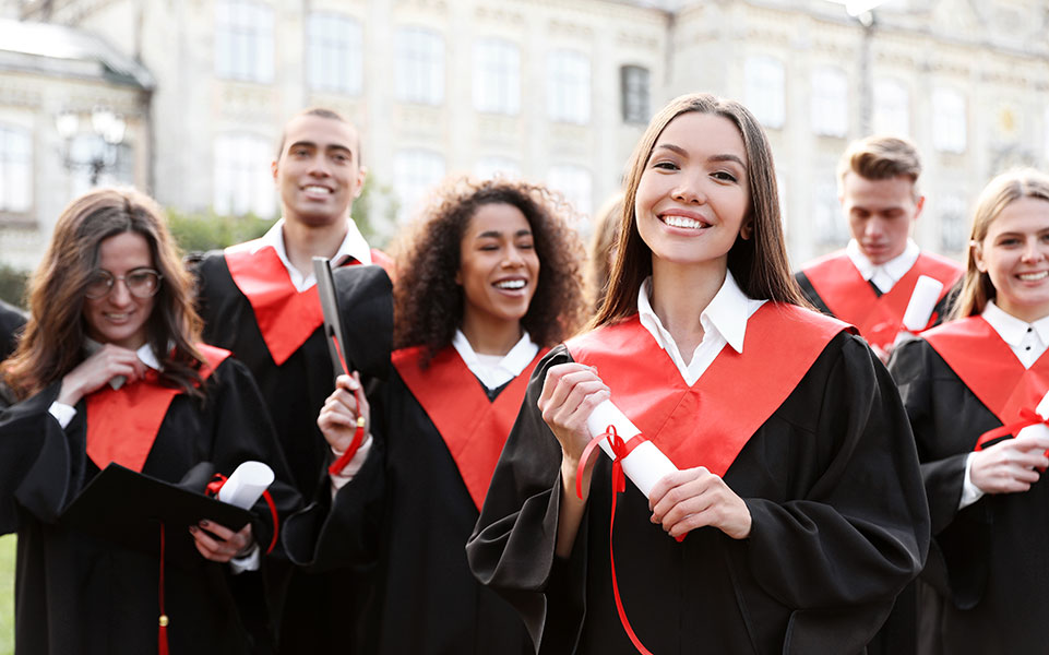 A group of master's degree graduates smile on graduation day.