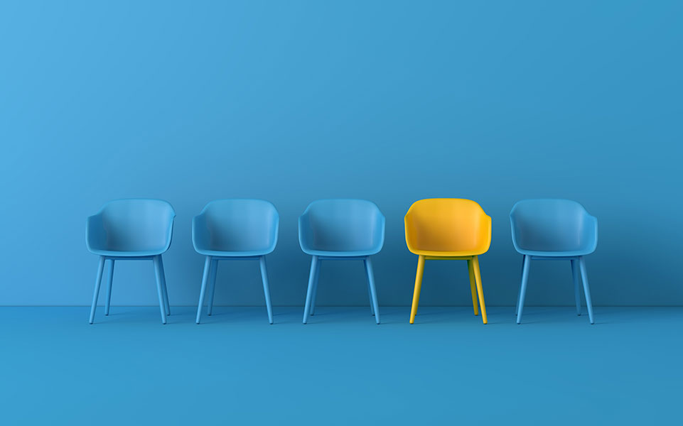 One yellow chair stands out among a group of blue chairs.